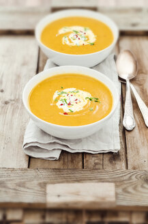 Two bowls of pumpkin soup on wooden tray, studio shot - CZF000111
