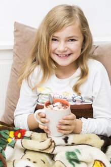Smiling little girl holding cup of cacao, studio shot - STB000146
