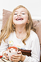 Smiling little girl covered with chocolate holding cup of cacao, studio shot - STB000159