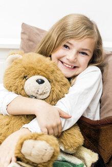 Little girl cuddling with her teddy bear, studio shot - STB000161