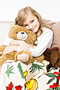 Smiling little girl cuddling with her teddy bear, studio shot - STB000163