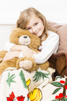 Smiling little girl cuddling with her teddy bear, studio shot - STB000163