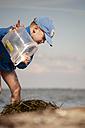 Germany, Schleswig-Holstein, Flensburg Fiord, Boy at  beach with bucket - JEDF000038
