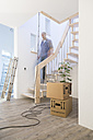 Man on staircase in new home - FKF000301