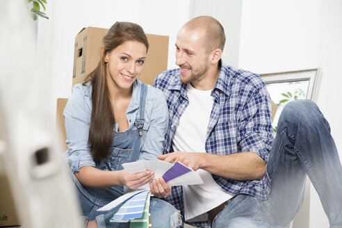 Young couple moving into new home, discussing color sample - FKF000326