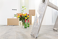Cardboard boxes, champagne and bunch of flowers in new home - FKF000332