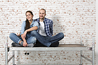 Young couple moving into new home, sitting on rack - FKF000335