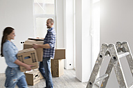 Young couple moving into new home, carrying cardboard boxes - FKF000340