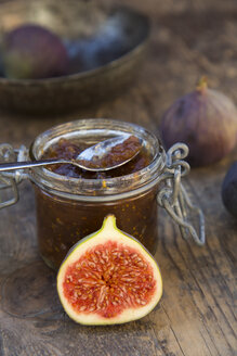 Sliced fig, whole figs (Ficus carica) and a glass of fig jam on wooden table, studio shot - LV000307