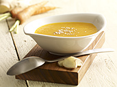 Carrot ginger soup on wooden board - SRSF000357