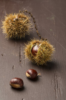 Sweet chestnuts on wooden table - MY000083