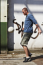 Man playing street soccer - STKF000681