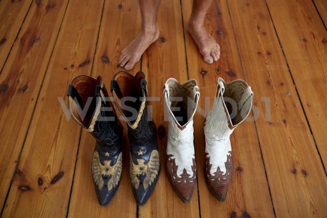 Germany, Berlin, Cowboy boots on wooden floor, bare feet in background - TKF000220