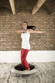 Germany, Bavaria, Woman jumping on trampoline - RNF001296