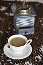 Cup of coffee, old coffee mill and coffee beans on table - SARF000134