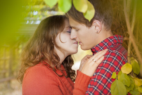 Happy young couple kissing in a park - BGF000025