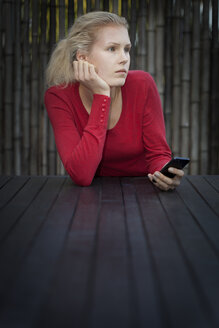 Young woman with smart phone sitting at garden table - BG000044