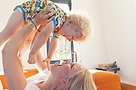 Mother holding baby boy aloft - MFF000670