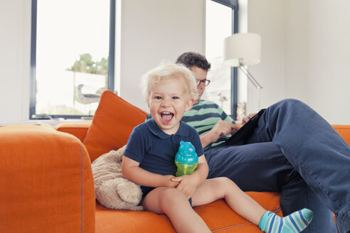 Little boy and his father sitting on the sofa - MFF000672