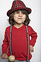 Portrait of smiling little boy with wooden rattle wearing hat and suspenders - FSF000311