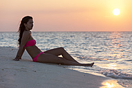 Maledives, young woman sitting at beach - AMF001243