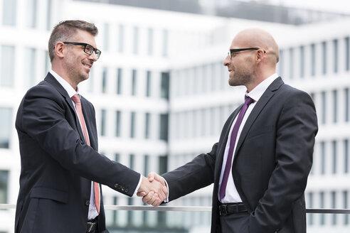 Poland, Warzawa, two businessmen shaking hands - MLF000272
