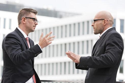 Poland, Warzawa, two businessmen gesturing - MLF000275