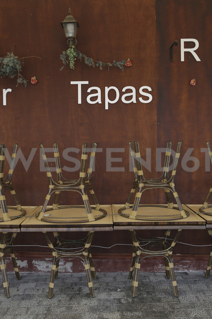 Spain, Lanzarote,Puerto del Carmen, Stacked tables and chairs in ront of Tapas bar - JAT000465