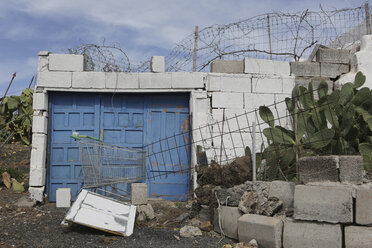 Spain, Lanzarote, Decaying buildig with cacti and litter - JAT000438