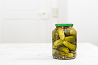 Glass of pickled cucumbers on white wooden table - DRF000283