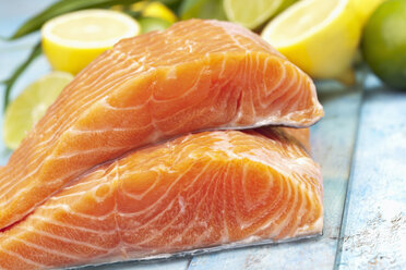 Salmon fillets (Salmo salar) and lemons on blue wooden table - CSF020332