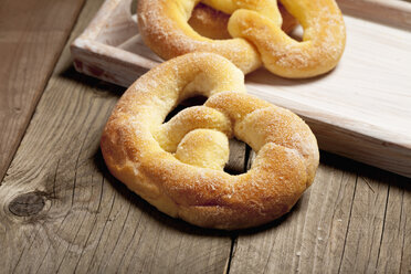 Two sugar pretzels and a tray on wooden table - CSF020340