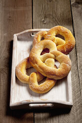 Three sugar pretzels and a tray on wooden table - CSF020342
