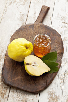 One and a half quince (Cydonia oblonga) and a glass of quince marmalade on wooden chopping board - CS020346