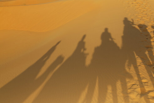 Africa, Morocco, Erfoud, Shadows of a caravan with camels and tourists on sand - GF000309