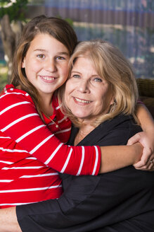 Senior woman and her granddaughter side by side - ABAF001069