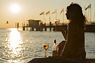 Germany, Bavaria, Nonnenhorn, Woman with wine on the bank of Lake Constance - SH001024