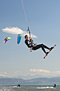Germany, Baden-Wuerttemberg, Fischbach, Kitesurfer mid-air above Lake Constance - SH001029