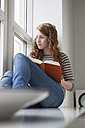Germany, Munich, Woman sitting on window sill, reading book - RBF001433