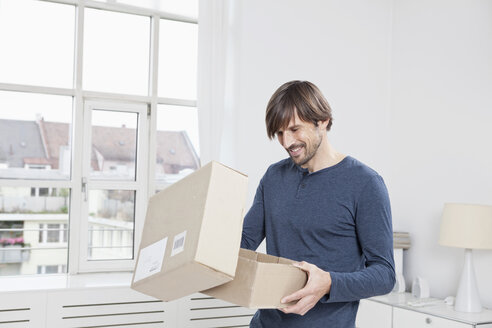 Germany, Munich, Man unpacking cardboard box - RBF001475