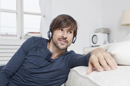Germany, Munich, Man sitting on sofa, wearing head phones - RBF001481