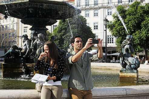 Portugal, Lisboa, Baixa, Rossio, Praca Dom Pedro IV, young couple with city map and smart phone in front of a fountain - BIF000053