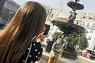 Portugal, Lisboa, Baixa, Rossio, Praca Dom Pedro IV, young couple photographing in front of a fountain - BIF000038