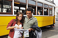Portugal, Lisboa, Baixa, Rossio, young couple with city map in front of tram - BIF000064