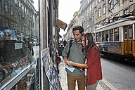 Portugal, Lisboa, Baixa, Rossio, young couple looking at postcards - BIF000066