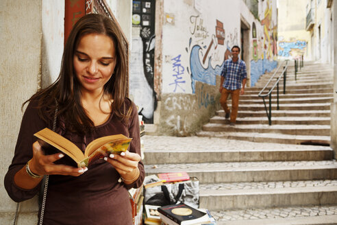 Portugal, Lisboa, Baixa, Rua do Madalena, young woman with book standing in front of antiquarian bookshop - BI000020