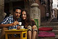 Portugal, Lisboa, Bairro Alto, young couple sitting at street cafe at dusk - BI000016