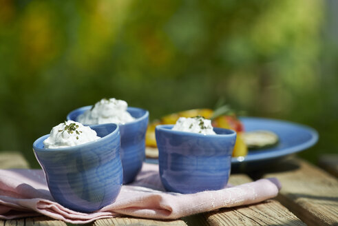 Bowls of curd with herbs on garden table - SRSF000405