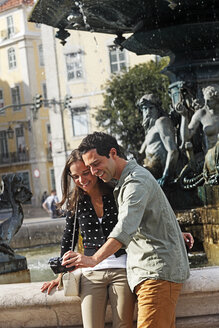 Portugal, Lisboa, Baixa, Rossio, Praca Dom Pedro IV, young couple photographing themself in front of a fountain - BIF000011