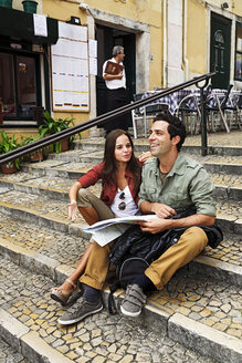 Portugal, Lisboa, Carmo, Calcada du Duque, young couple with city map sitting at stairs - BI000009
